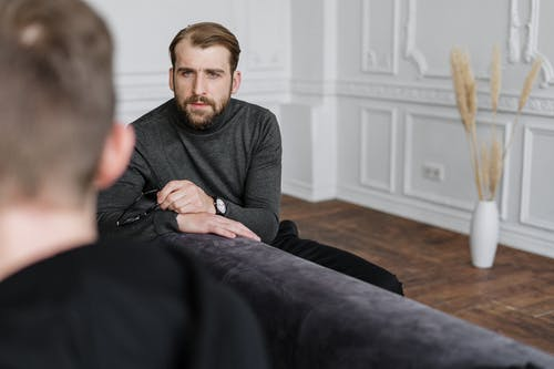 Man in Gray Sweater Sitting on Black Couch
