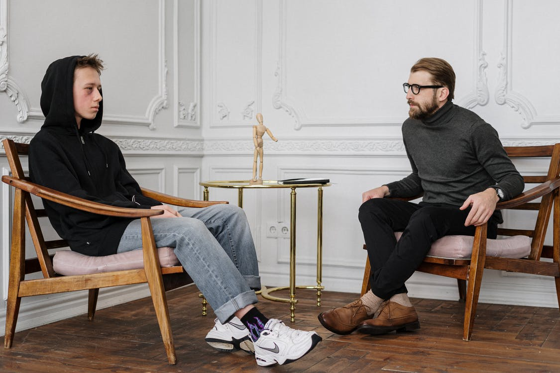 Man in Black Sweater and Blue Denim Jeans Sitting on Brown Wooden Chair