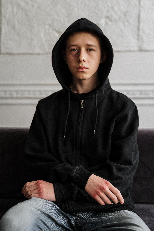 man in black hoodie sitting on black couch