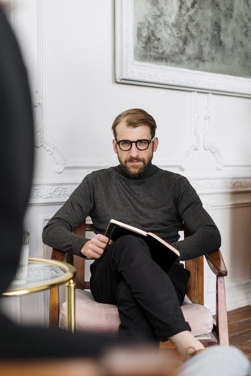 Man in Gray Sweater Sitting on Chair