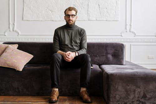 Man in Black Sweater and Black Pants Sitting on Gray Couch