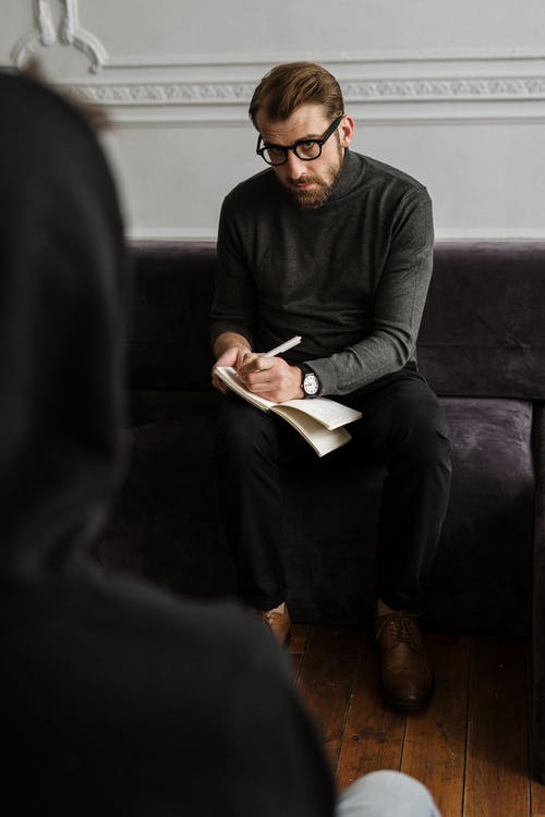 Man in Black Long Sleeve Shirt and Black Pants Sitting on Black Sofa