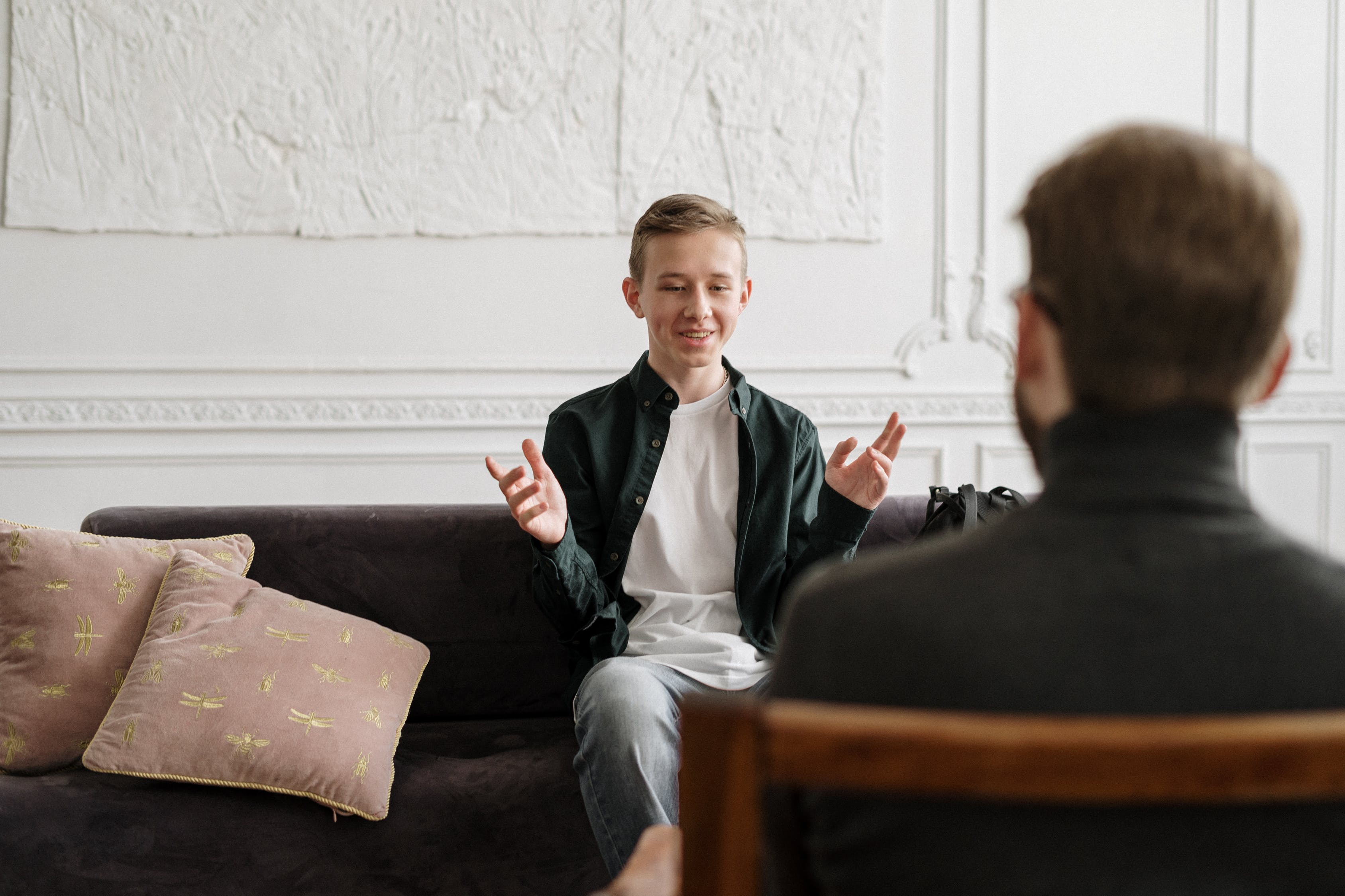 A teenage boy sits on a couch facing a therapist listening to him talk in the foreground. Used courtesy of pexels.com