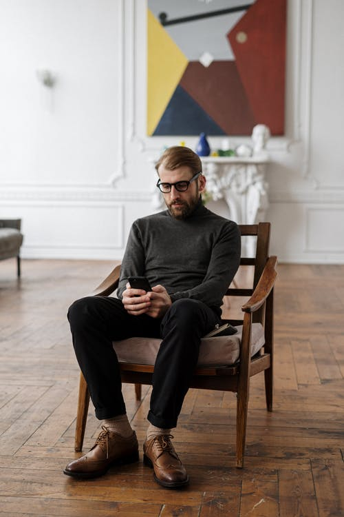 Man in Black Sweater Sitting on Brown Wooden Armchair