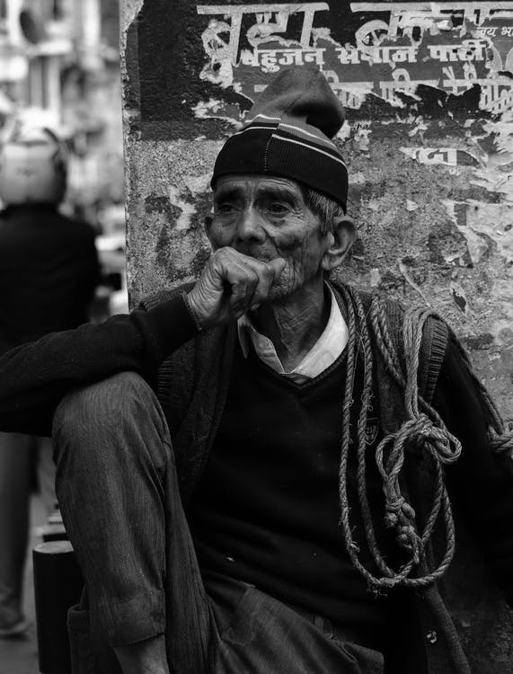 Ethnic old man sitting next to shabby wall