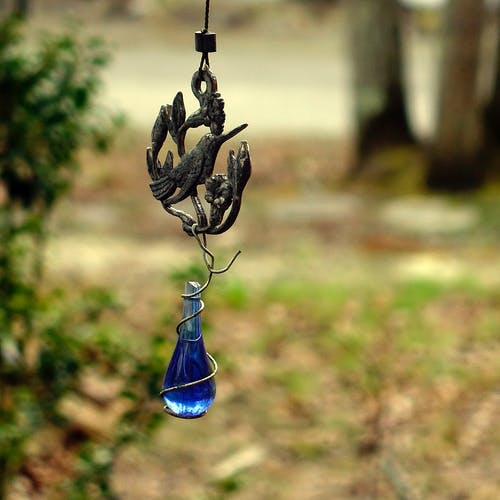 Metal decoration in shape of bird with ornament and bright blue crystal hanging on street against forest