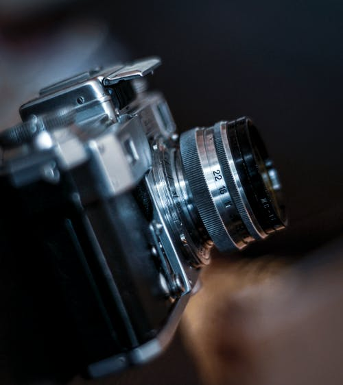Closeup of professional cool retro photo camera on blurred background of workshop interior