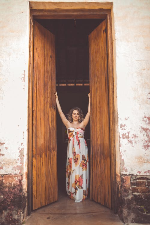 Woman in White and Red Floral Dress Standing in Front of Brown Wooden Door