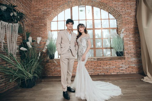 Young Asian just married couple in wedding clothes