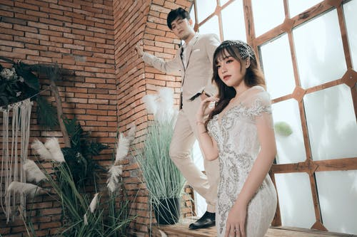 Pensive Asian well dressed groom leaning hand to wall and looking at charming slender fiance with makeup in elegant white bridal gown looking away in cozy room decorated with plants