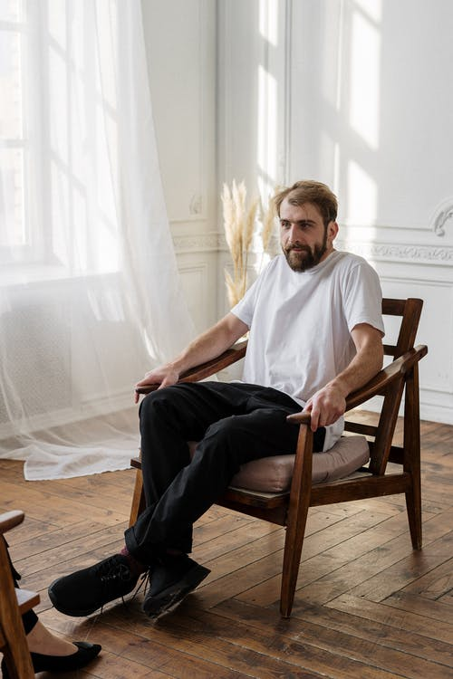 Man in White Crew Neck T-shirt Sitting on Brown Wooden Armchair