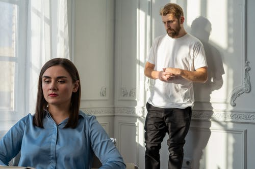 Man in Blue Polo Shirt and Black Pants Standing Beside Woman in White Long Sleeve Shirt