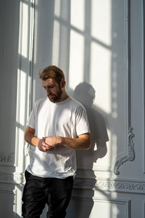 Man in White Crew Neck T-shirt Standing Beside Window
