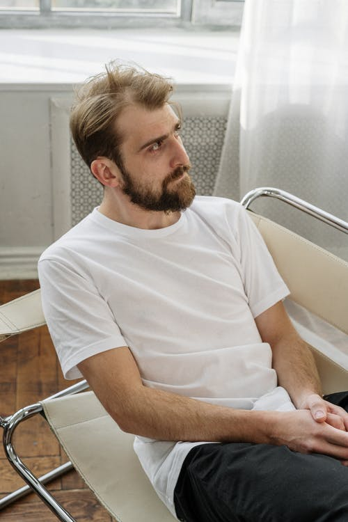 Man in White Crew Neck T-shirt Sitting on White Chair