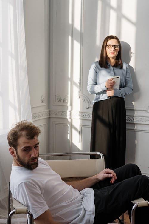 Man in White Dress Shirt Sitting Beside Woman in Black Dress
