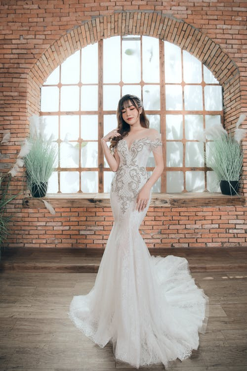 Full body of thoughtful young Asian bride in long elegant white wedding dress looking down in bright studio decorated with pot plants