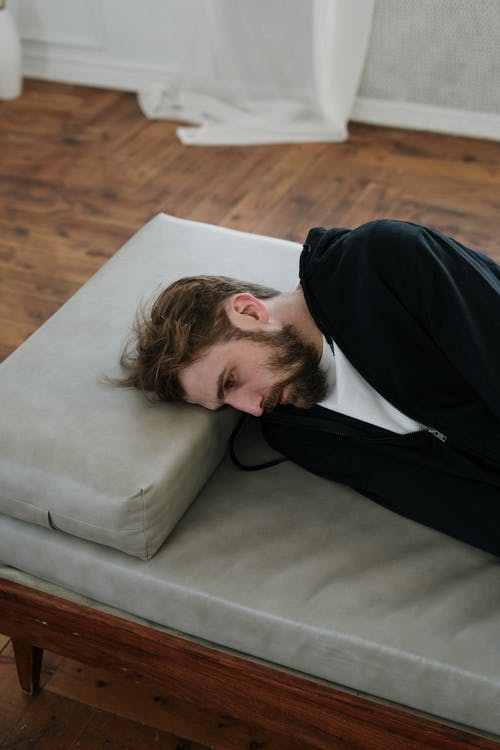 Man in Black Long Sleeve Shirt Lying on Gray Couch