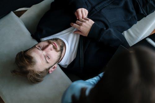 Man in Black Jacket Lying on White Pillow