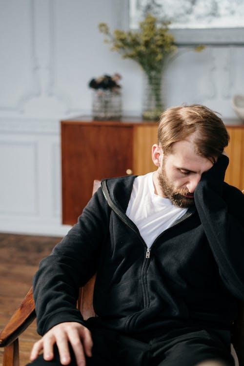 Man in Black Zip Up Jacket Sitting on Chair
