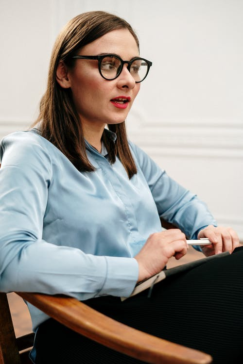 Woman in Blue Dress Shirt Wearing Black Framed Eyeglasses