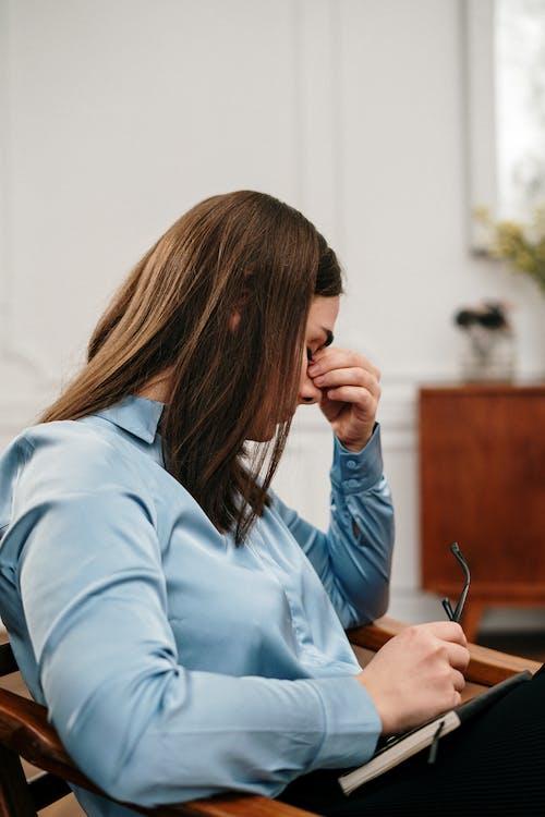 Woman in Blue Long Sleeve Shirt Holding Pen