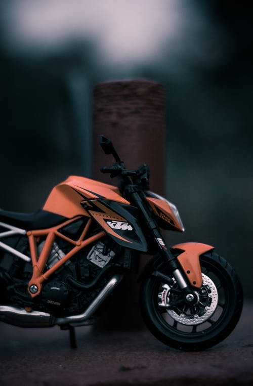 Closeup of small black orange motorcycle with black wheels next to metal pillar on blurred background