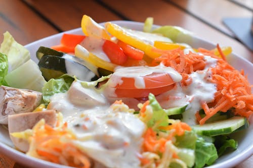 Salad of fresh grated carrots and cut tomato with lettuce and slices of hum covered with white dressing