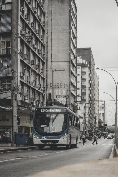 White and Blue Bus on Road Near Building
