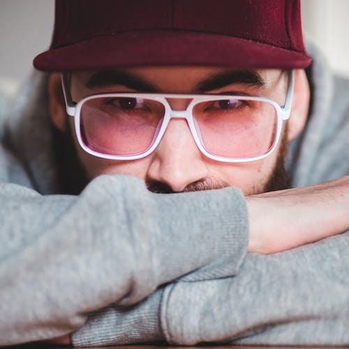 Emotionless bearded man in purple hat