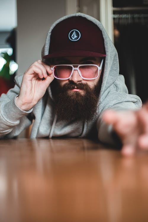 Serious male hipster with bushy beard in warm gray hoodie and purple hat confidently looking at camera over pink transparent eyeglasses