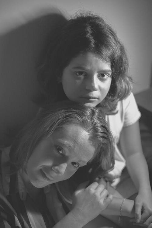 Black and white young mother resting on shoulder of pensive daughter and looking at camera