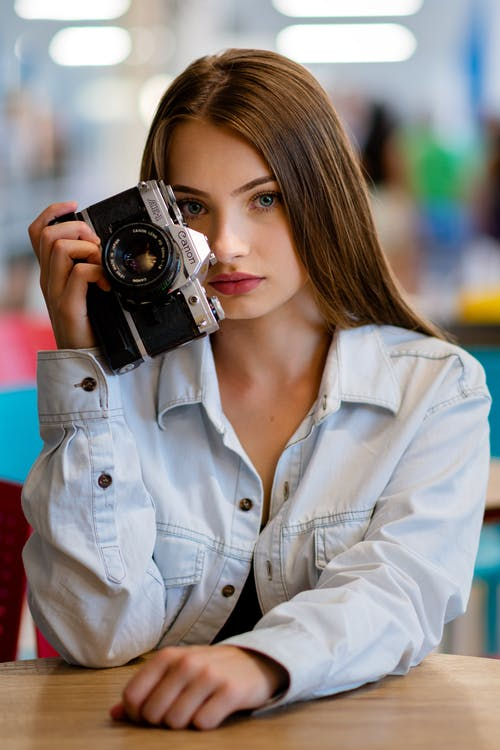 Young female photographer demonstrating old photo camera and looking at camera while lounging in bright room on blurred background