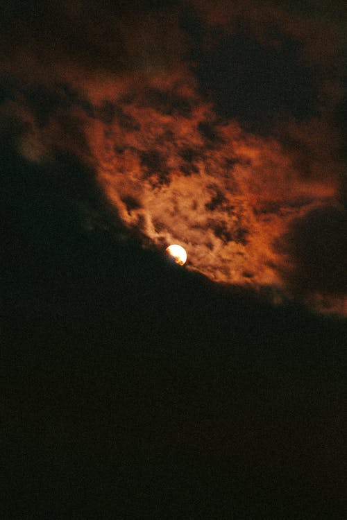 Moon in night sky surrounded by orange cloud