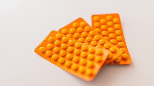 Orange packages of medications on table