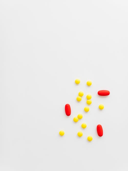 Yellow and red medications on white background
