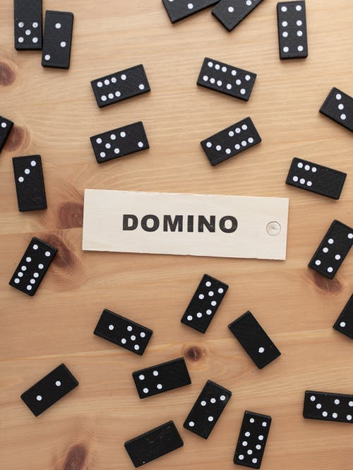Small black dominoes on wooden table