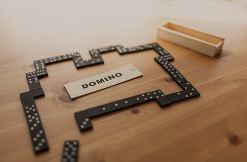 Arrangements of small black dominoes with white dots on surface and wooden box on table in sunlight