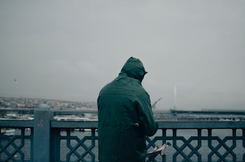 Back view of anonymous fisherman in dark green raincoat with hood standing on coast of lake behind fence and catching fish