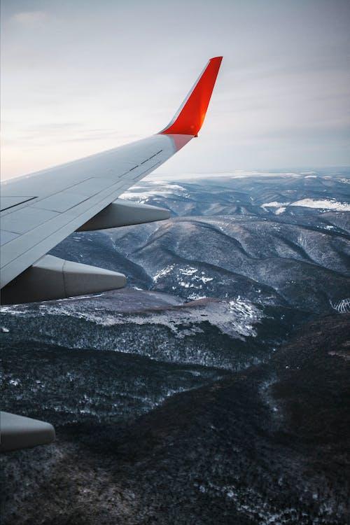 雪に覆われた山々の上の白と赤の飛行機の翼