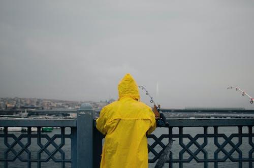 Faceless man fishing on coast of lake in city