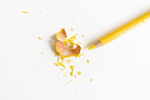Top view of bright pencil with pointed shaft near dry wavy shavings and tiny fragile parts on white surface