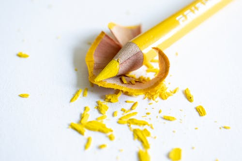 Sharpened bright yellow pencil with shavings on white surface