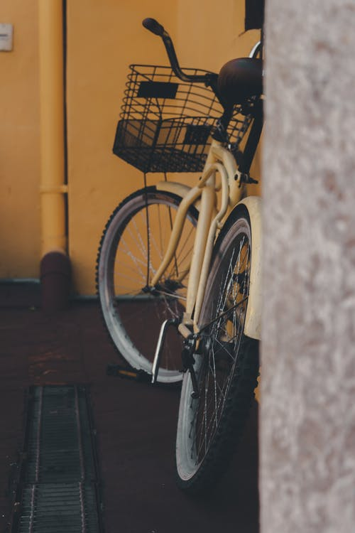 Black Bicycle Leaning on Yellow Wall