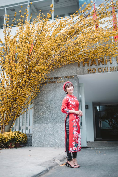 Woman in Red and White Floral Hijab Standing Beside Brown Tree