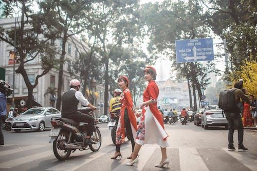 Woman in Red Dress Standing on Sidewalk
