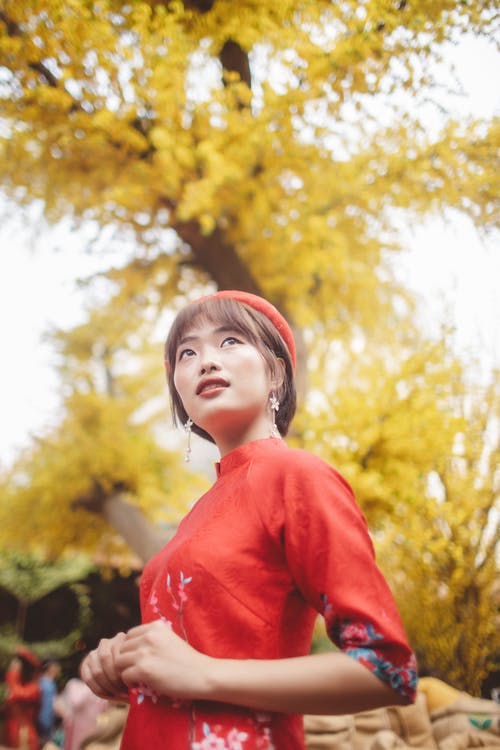 Girl in Red Long Sleeve Shirt Standing Near Green Trees