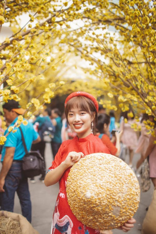 Girl in Red Shirt Holding Brown Round Fruit