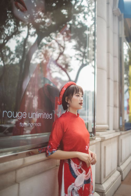 Woman in Red Crew Neck T-shirt Standing Beside Glass Window