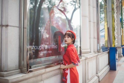 Woman in Red and White Dress Standing Near Glass Window