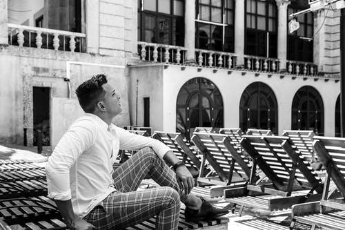 Black and white side view of fit contemplative male in stylish outfit with creative haircut looking away while sitting on sunbed near aged house with decorative fence and arched doors